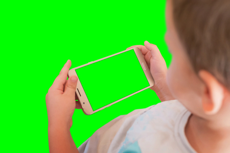 Kid watching video or play game on smart phone. Isoalted screen and background in green, chroma key. Stock Photo