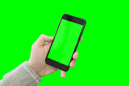 Modern smart phone ih man hand. Close-up. Isolated in green. Stock Photo