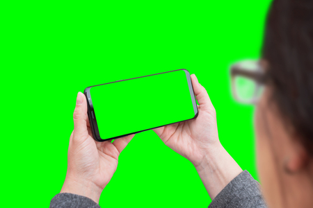 Woman use modern smart phone in horizontal position. Isolated in green, chroma key.