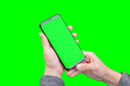 Phone in woman hands isolated in green, chroma key.