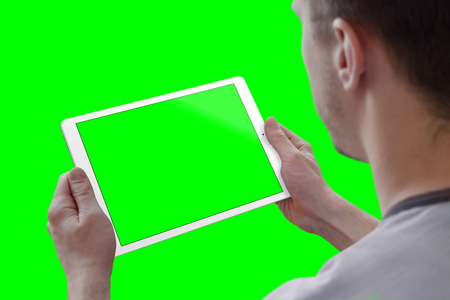 Man holding tablet in horizontal position. View over the shoulder. Isolated screen for mockup, and background in green for video editors. Stock Photo