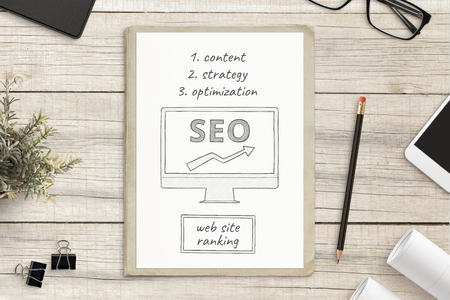 Search engine optimization sketch on white paper surrounded with office supplies. SEO web site concept. Stok Fotoğraf