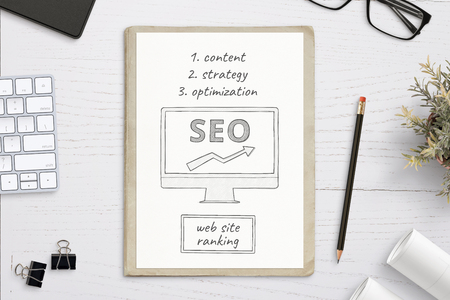 SEO sketch goals on white paper. Keyboard, glasses, plant, projects, pen, folder, clips beside. Top view, flat lay, hero, header image.