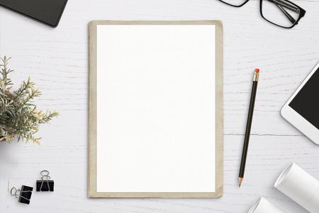 Empty paper mockup, on old folder, white wooden work desk. Top view, flat lay.