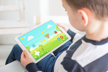 Boy playing game on white tablet. Home interior in bacgkround. Kid games on mobile devices concept.