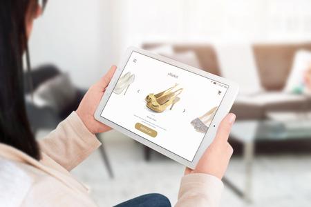 Kobieta zakupy online z tabletem. Nowoczesny interfejs witryny handlowej z butami. Zdjęcie Seryjne