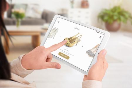 La niña agrega zapatos al carrito de compras con la aplicación en línea. Concepto de tienda online.