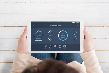 Modern, automated home control app with artificial intelligence on tablet display in woman hands. Top view. Wooden floor in background. Фото со стока