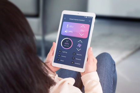 Smart home control automation app concept. Woman use tablet with modern flat desing app to control living room temperature, ventilation, lighting.