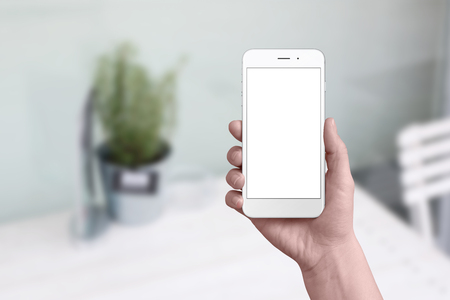 Simple white phone mockup in woman hand. Flat background with table and plant. Isolated screen for add app user interface design.