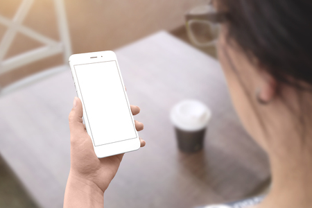 Woman hold white smart phone with isolated screen for mockup. Coffee shop table in background.