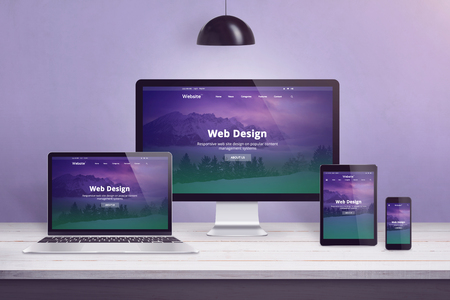 Flat design web site concept on multiple devices. Work desk with laptop, computer display, smart phone and tablet. Purple wall in bacground.