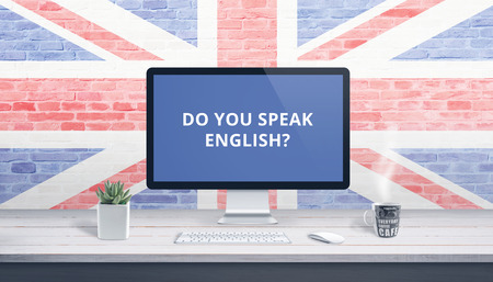 Do you speak English on computer display with a flag of Great Britain in the background. Online lessons concept. Banco de Imagens