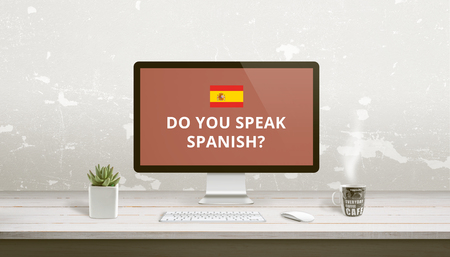 Concept of Spanish language learning online. Question Do you speak Spanish on a computer display on work desk. Banco de Imagens