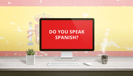 Do you speak Spanish on computer display with a flag of Spain in the background. Online lessons concept. Archivio Fotografico