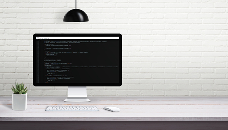 Computer programming on computer display with free space on brick wall for text.