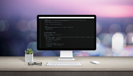 Concept of programming on a computer. Work desk with computer display and text editor. Stock Photo