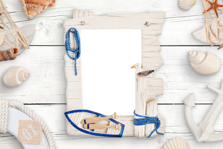 Summer travel photo family isolated frame for mockup surrounded with shells on white wooden table.
