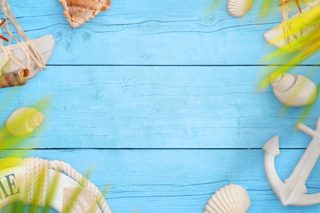 Summer sea travel background. Shells, belt and anchor on blue wooden table. Space for text in the middle.