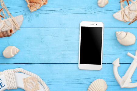 Phone mockup on blue wooden table surrounded with sea shells, anchor, boat life belt. Concept of use mobile phone on summer, beach travel. Stock Photo