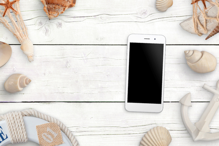 Mobile phone with blank screen for mockup on white wooden table surrounded with shells and sea anchor, boar life belt. Stock Photo