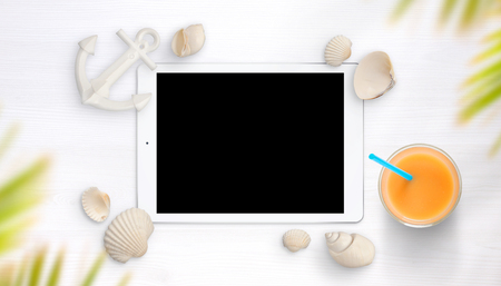 Tablet surrounded with shells on white table. Juice and small boat anchor beside. Palm tree above. Stock Photo