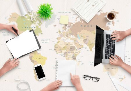 Travel agency office concept. People work with papers and a computer. World map in the background. Flat lay, top view.