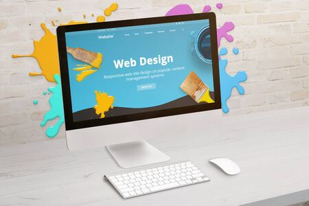 Concept of web design studio with coimputer display and color drops on brick wall. Modern web design teme on screen. Concept of modern graphic studio desk.