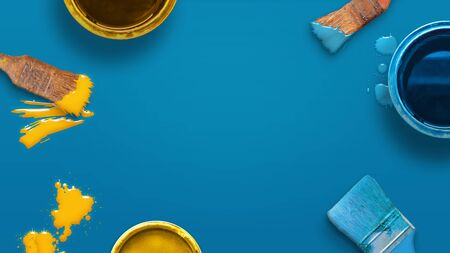 Prepare fot painting concept with color brushes and color boxes on blue surface. Top view, flat lay, close-up.