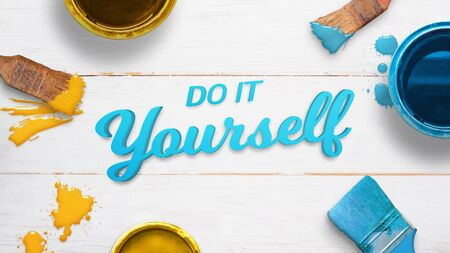 Do it yourself text on a white wooden table surrounded by color brushes, boxes and few color drops. Flat lay, top view, close-up.