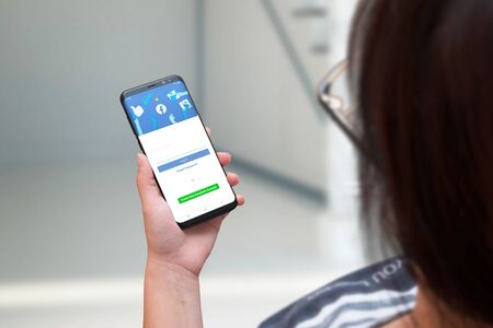 SARAJEVO, BOSNIA AND HERZEGOVINA - JULY 14, 2019: Woman holding smart phone with a new redesigned version of Facebook. The concept of progress and social network changes. Editorial
