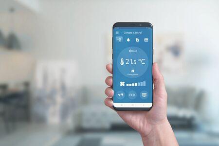 Slimme telefoon ter beschikking met app voor klimaatbeheersing. Concept van automatisering van omgevingscomfort met een eenvoudige telefoon-app.