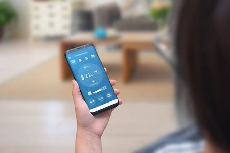 Woman use climate control app on a phone in the living room to adjust temperature and ventilation.