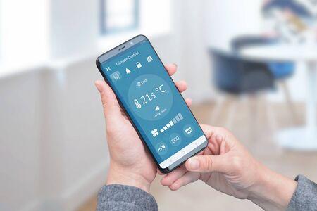 Warmteregeling in huis met simpele app op telefoon voor afstandsbediening van airco's. Het concept van energie-efficiëntie, besparingen en ecologie.