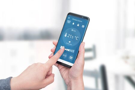 Smart home climate control app on phone display concept. Woman holding a phone and adjust temperature and ventilation. Close-up. 写真素材