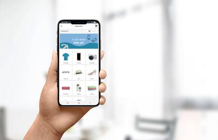 Lo shopping online a casa concetto. Donna che tiene il telefono e usa il moderno sito web del negozio online per i prodotti pinna.