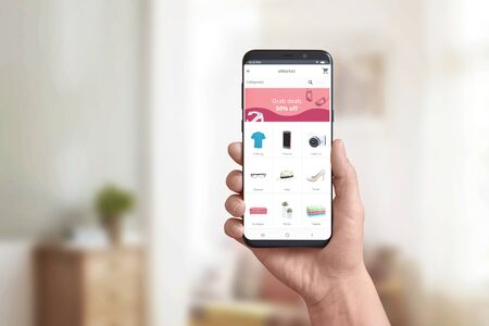 Hand showing online store app on a modern smart phone. Concept of online shopping and grab deals, discount marketing. Product categories and shopping cart.