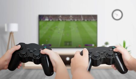 Boys play soccer on the gaming console on a large TV in the room. The concept of fun and gaming for friends. Archivio Fotografico