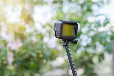 Action camera on tripod, selfie stick makes footage. Blank creen for mockup. Tree in background. Banco de Imagens - 129312601