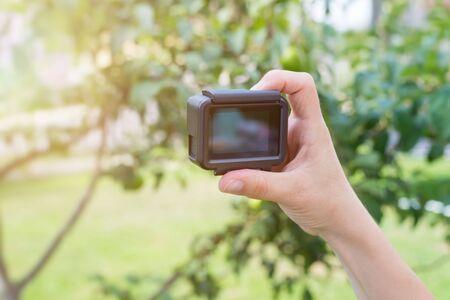 Action camera mockup in woman hand. Close-up.