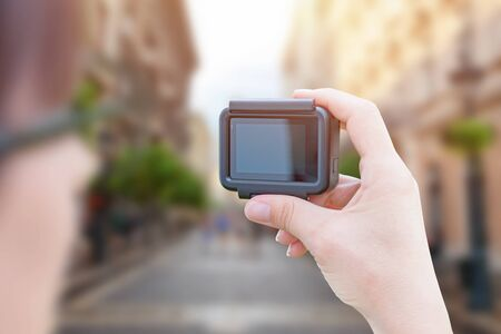 Influencer makes video with action camera in city street concept. Banco de Imagens