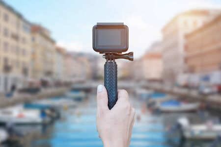 Action camera on stick in hand recording city concept. Blank screen for mockup. Banco de Imagens - 129312666