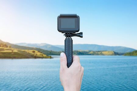 Hand hold stick and action camera and recording lake. Blank screen for mockup. Filmmaking concept.