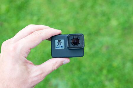 Action camera in hand close-up. Lens and small display with resolution, battery and memory card information.