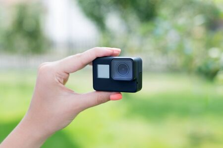 Making a selfie with action camera concept. Camera in woman hand. Close-up.