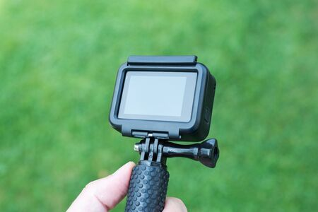 Action camera close-up on stick. Blank screen for mockup.