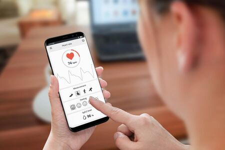 Heart rate and oxygen measure concept. Woman use phone and sensor in office to monitoring health.