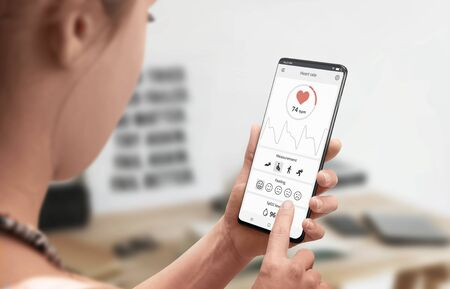 Measuring heart rate with mobile app and sensor on a mobile phone concept. Close-up. 版權商用圖片