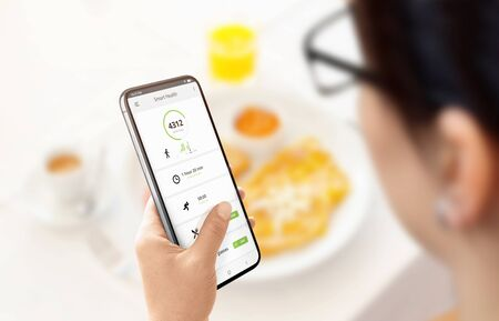 Girl calculates calories burned and consumed on app on modern smart phone. Lunch in background. Concept. Banco de Imagens