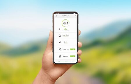 App for measuring mileage and calories burned concept. Modern smart phone in woman hand. Nature landscape in background.